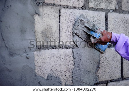 The work of a plasterer by applying plaster to the wall to have a smooth surface. #1384002290