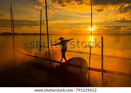 The work of fishermen on the Mekong River raft during the sunrise is a hustling and indigenous way of life in Nong Khai province, opposite to Vientiane Laos.
