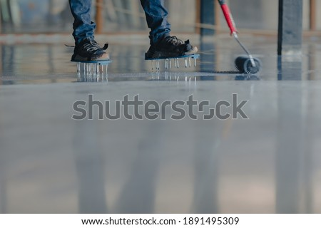 The worker applies gray epoxy resin to the new floor Foto stock ©