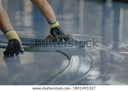The worker applies gray epoxy resin to the new floor Сток-фото ©