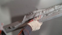 The worker applies the mortar to the wall with a wire. Spatula with mortar. Construction worker puts a plaster on the wall with a trowel