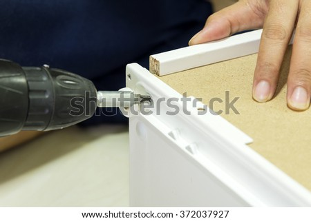The worker assembling install the hing of  the furniture door by using the power screw driver.