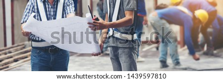 The worker builder foreman engineering occupation working with construction site project background. person looking plan paper to made floor business tower building. industry building concept.