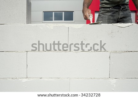The worker builds wall using big white bricks