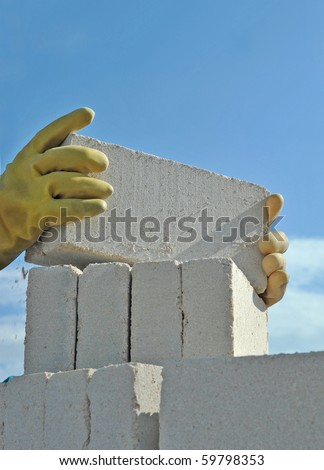 The worker builds wall using  white bricks