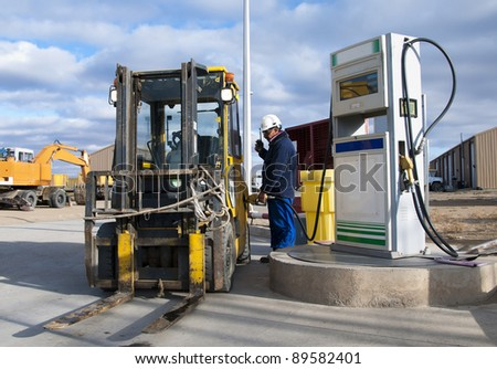 The worker fills with fuel a loader