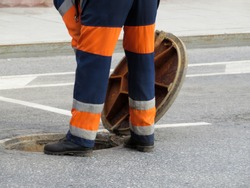 The worker in uniform stand over the open sewer hatch. Repair of sewage or underground utilities
