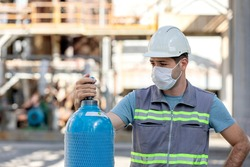 The worker is checking to the industrial compressed gas cylinder in the factory. A gas cylinder is a pressure vessel for storage and containment of gases at above atmospheric pressure.