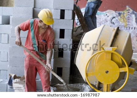 The worker is standing beside a concrete mixer.  He is filling his wheel barrel.  Horizontally framed shot.