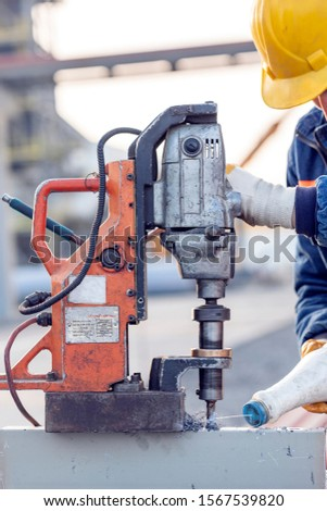 The worker is working with magnetic drill machine. It is a portable drilling machine with a magnetic base. It can use twist drill bits, annular cutters, milling cutters, and other rotary cutters.  #1567539820