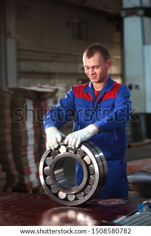 The worker manually packs the finished bearing. Bearing production concept. Photo in the interior of the plant. Portrait of a man in overalls.