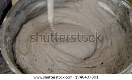 The worker mixes the mortar. Wet Concrete or motrar mixing texture. Gray mortar, concrete surface. The solution is stirred, apartment renovation. Foto stock ©