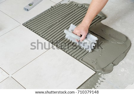 The worker's hand is putting tiles adhesive to the wall with the notched trowel.