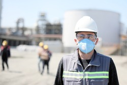 The worker (staff, engineer) protects himself from covid-19 (coronavirus) with a protective mask in the construction site.
