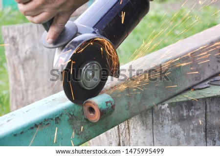 The worker uses an angle grinder producing many sparks.