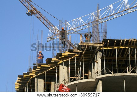 The workers connecting armature on a building site against the dark blue sky