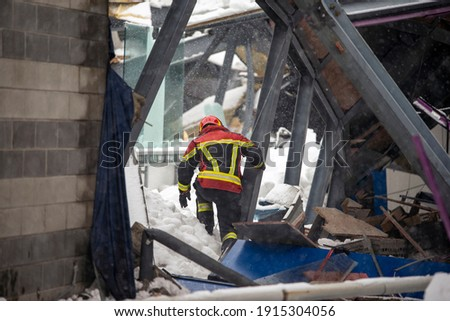 The working moments of the search and rescue teams who were under the rubble in the roof collapse under the weight of snow. Firefighters inside a collapsed house are looking for survivors. Stock photo ©
