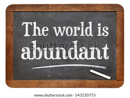 The world is abundant - white chalk text on a vintage slate blackboard