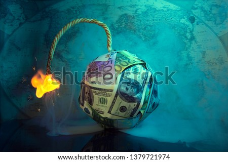 The world of money is burning.Financial bomb explodes.Smoke,fuse.Dollar and Euro decrease. Global economic recession concept.World map in the background.