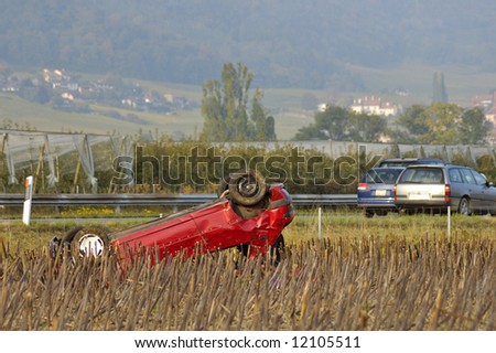 The wreck of a car, upside down beside a motorway (freeway, autoroute, autobahn) - stock photo