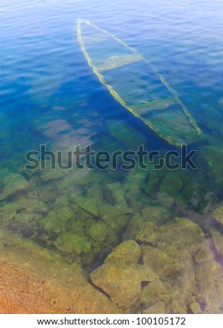 The wreck of a ship lying at the bottom.Natural water background.