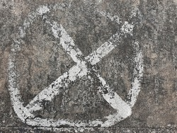 The X symbol is surrounded by a circle drawn from white on a street or a pedestrian. It is an indication that standing, parking, or placing things in the area is strictly prohibited.