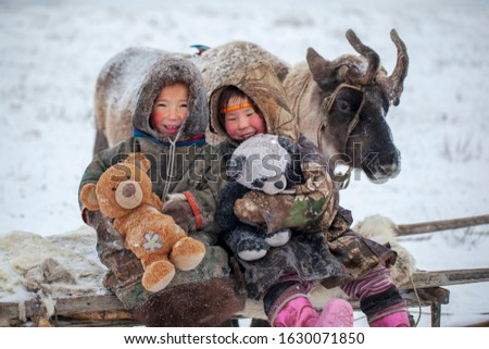 The Yamal Peninsula, the extreme north. Happy boy and girl on reindeer herder pasture in a cold winter day, polar circle, children and animals.