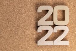 The year twenty twenty-two in large cardboard numbers on a cork background