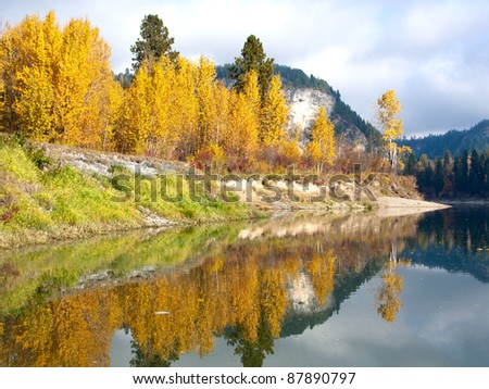 The yellow and green colors of Autumn reflect off the calm still water of the river.