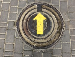 The yellow arrow indicates the forward direction. The sign is painted on a protective hatch above the sewer. Railway hatch on the road. Paving slabs are laid out around the hatch. The tiles are gray.