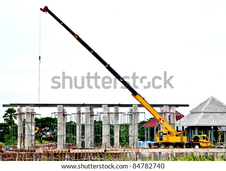 The yellow automobile crane lifted equipment for under construction