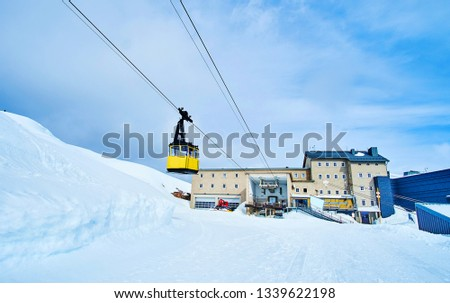 The yellow cabin of Dachstein-Krippenstein cable car circuit, covering mountain slopes and offering different routes for visitors and sportsmen, Salzkammergut, Austria.