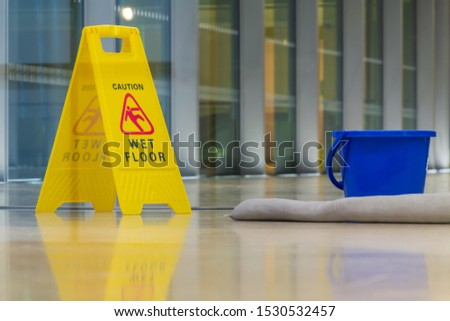 The yellow caution sign showing warning of slippery wet floor.
