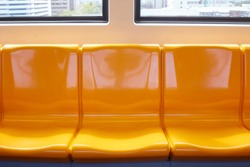 The yellow chair rows on the train in Thailand are empty.