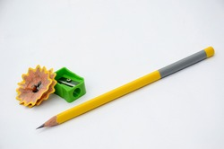 the yellow colour wooden peels pencil with waste flower and green sharpner isolated on white background.