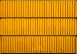 The yellow gold surface texture of the sea container. Three stacked containers without labels.