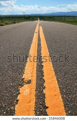 the yellow lines of a rural Colorado road lead off towards the distant horizon