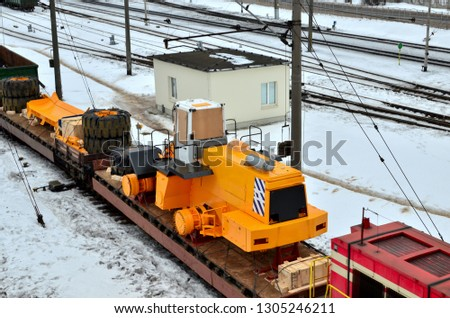 The yellow mining truck and front loader disassembled into parts is loaded onto a cargo railway platform. Logistics of delivery of the truck, transportation of heavy heavy machinery