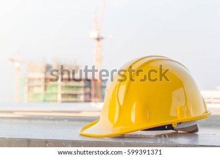 The yellow safety helmet at construction site with crane background