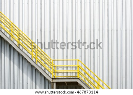 The yellow stair for fire escape with the steel wall of the factory building.The factory wall building and the yellow stair building  #467873114