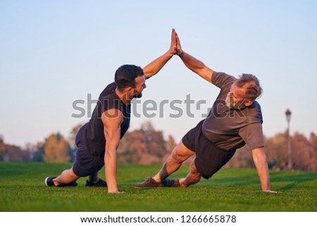 The young and old sportsmen push up together on the grass