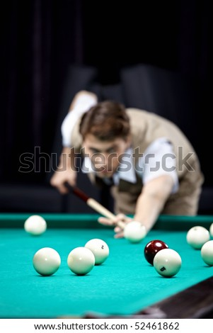 The young attractive well dressed man plays billiards