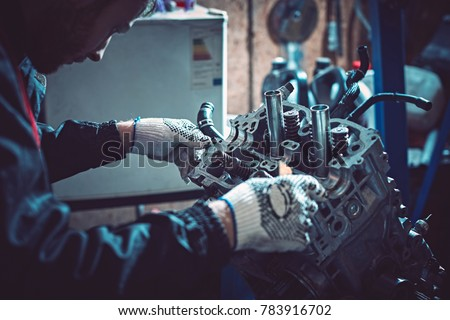 The young auto mechanic dismantles the opposing engine for diagnosis and repair at the stand in the workshop. #783916702