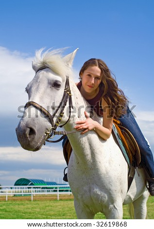 The young beautiful girl embraces a white horse