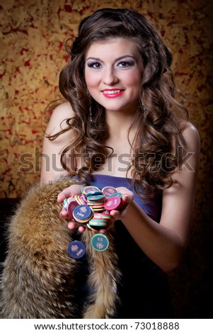 The young beautiful girl has won in poker. The young girl with chips in the hands - stock photo