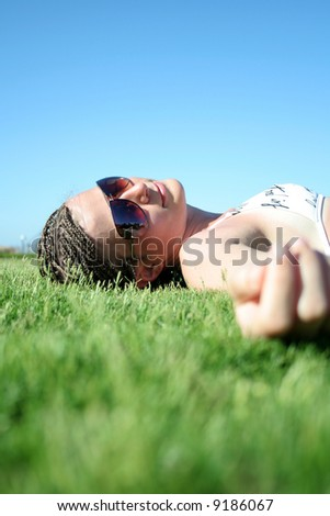 The young beautiful girl lays on a grass