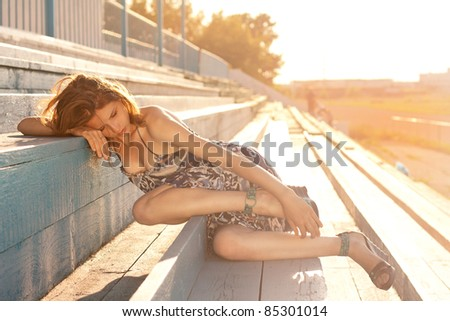The young beautiful girl lies on a hippodrome tribune in sunset beams