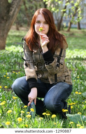 The young beautiful girl sits on a glade of dandelions