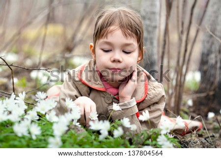 The young, beautiful girl walks in the woods. Lying they studied forest plants and flowers. Hands touching petals of flowers.