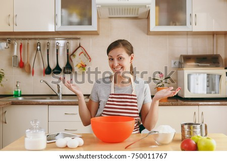 The young beautiful happy woman prepares dough for Christmas cakes with tablet on table in the kitchen. Cooking home. Prepare food. #750011767